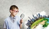 Cute school boy examining objects with magnifying glass. Elements of this image are furnished by NAS