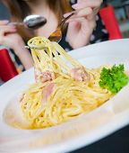 picture of carbonara  - Woman eating spaghetti carbonara bacon in white cream sauce - JPG
