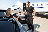 stock photo of superstars  - Bodyguard helping elegant woman stepping out of car at airport terminal - JPG