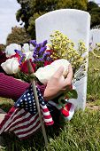 picture of headstones  - Headstones person placing floral arrangement and Flags at National Military Cemetery - JPG