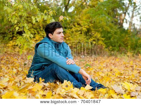 Young serious guy relaxing in park, autumn outdoor.