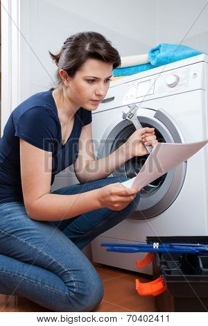Woman Trying To Repair Washing Machine