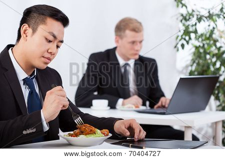 Businessmen Eating Healthy Meal In Office