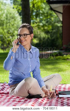 Woman Talks On Phone In Garden