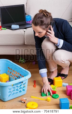 Businesswoman Picking Up Toys