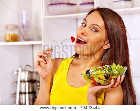 Happy woman eating salad at kitchen.