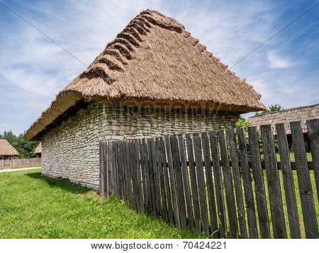 Farmstead with thatched cottage and picket fence shot against blue sky