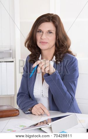 Portrait: Successful Middle-aged Attractive Woman Sitting In The Office.
