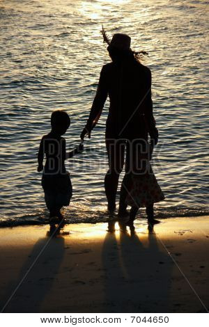 Silhouettes Of Mother And Two Kid On Sunset Sea Background