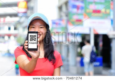 Young asian woman hold smart phone show quick response coupon code