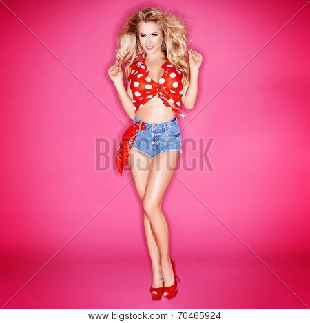 Cute beautiful blond woman in red polka dots and skimpy denim shorts twirling her long hair in her fingers as she smiles seductively at the camera  on pink