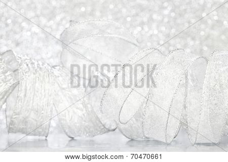 Curly silver serpentine on shiny glitter background, holiday concept