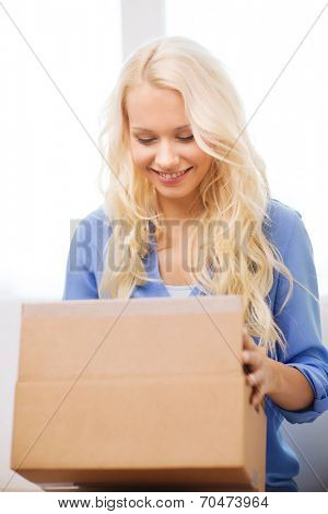 transportation, delivery, home and people concept - smiling woman opening cardboard box at home