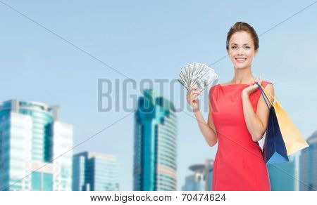 shopping, sale, gifts, money and holidays concept - smiling woman in red dress with shopping bags and money