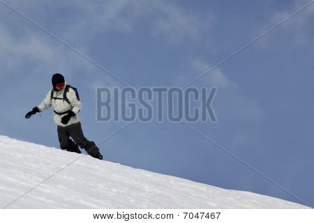 Single Snowboarder Sliding On A Blue Sky Background