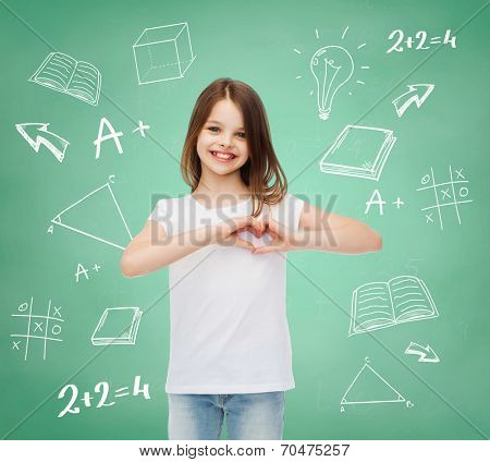 advertising, gesture, charity, education and people - smiling little girl in white blank t-shirt showing heart-shape gesture over green board with doodles background