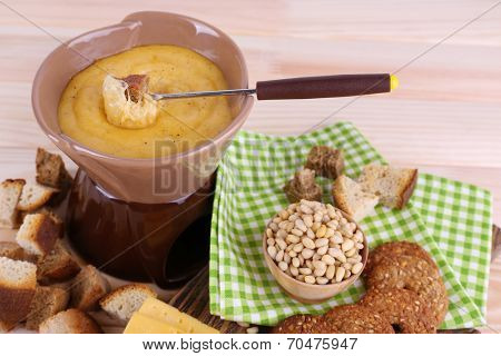 Fondue, biscuits, slices of cheese and rusks on cutting board on napkin on wooden background
