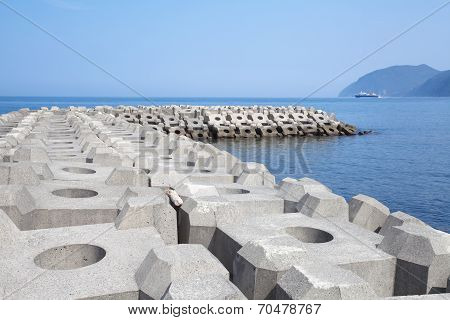Breakwater concrete dam with blue sea and sky background
