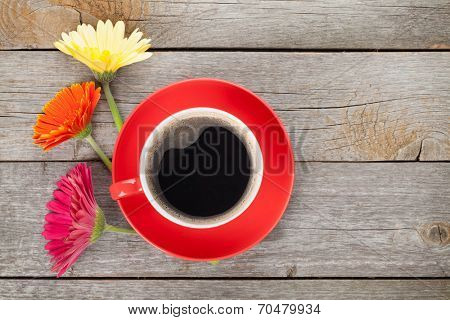 Cup of coffee and gerbera flowers on wooden table