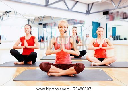 fitness, sport, training, gym and lifestyle concept - group of smiling female with trainer meditating in the gym