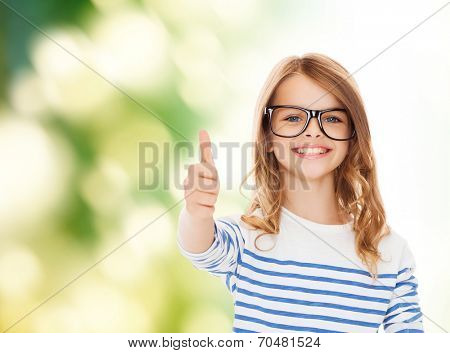 education, school and vision concept - smiling cute little girl with black eyeglasses showing thumbs up gesture