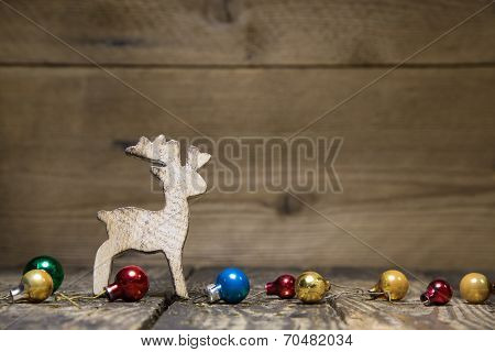 Wooden Elk Or Reindeer On A Old Rustic Country Style, Background With Old Christmas Balls For A Natu