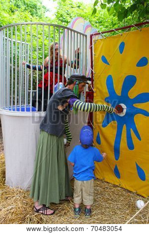 MUSKOGEE, OK - MAY 24: A man dressed as a woman calls people for a game of dunk tank at the Oklahoma 19th annual Renaissance Festival on May 24, 2014 at the Castle of Muskogee in Muskogee, OK