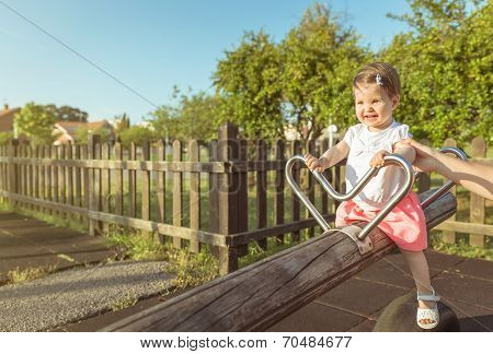Baby girl playing over a seesaw swing on the park