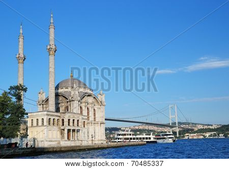 ISTANBUL, TURKEY - AUGUST 7, 2007: Fishermen under the Ortakoy mosque against the Bosporus bridge. The mosque was built in 1856 in the Neo-Baroque style by design of father and son Balyan