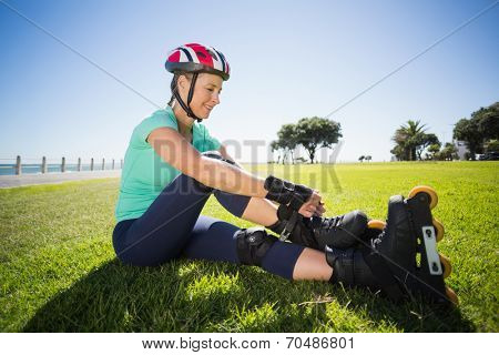 Fit mature woman tying her roller blades on the grass on a sunny day