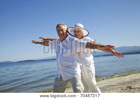 Mature couple having fun on ocean beach