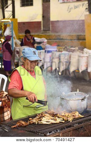 Roasting Chicken Legs at Market in Banos, Ecuador