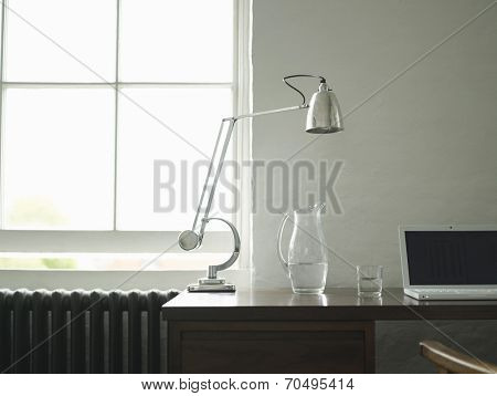 Closeup view of a study desk with laptop and lamp