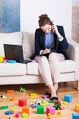 foto of toy phone  - Working woman talking on phone among child - JPG