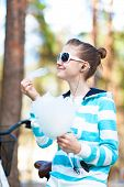 stock photo of candy cotton  - Smiling happy girl in sportswear in spring park eating cotton candy - JPG