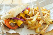 stock photo of cheese-steak  - Philly cheese steak sandwich with fries takeaway