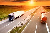 stock photo of cistern  - Two trucks in motion blur on the highway at sunset - JPG