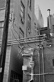 foto of modification  - An urban alley shows electronic and electrical modifications made over the years resulting in a tangle of exposed conduit - JPG