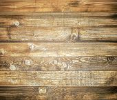 pic of log fence  - Background of brown old natural wood planks Dark aged empty rural room with tree floor pattern texture Closeup view to golden surface of retro pine logs inside vintage light warm interior with shadows - JPG