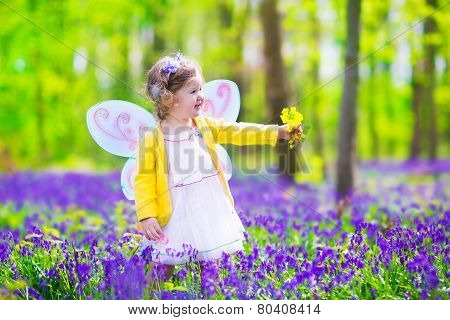 Little Girl In Fairy Costume In Blue Bell Field