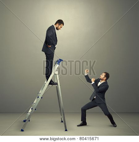 displeased businessman on the stepladder looking down at man in fighting stance. photo in the grey studio