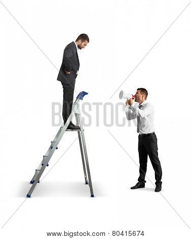 aggressive businessman with megaphone screaming at man on the stepladder. isolated on white background