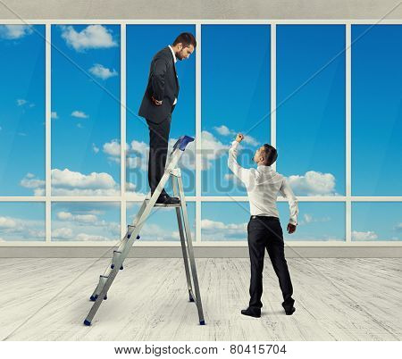 discontented businessman standing on stepladder and looking at angry screaming man. photo in the room with big windows
