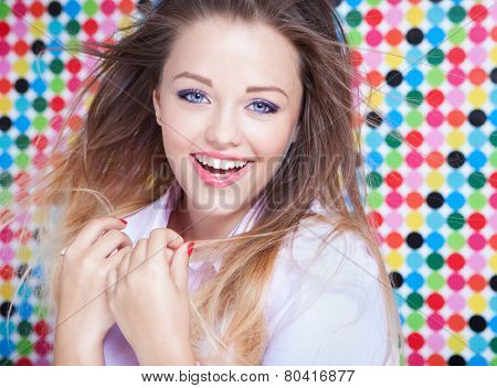 Attractive young laughing woman on spotted background, beauty and fashion concept