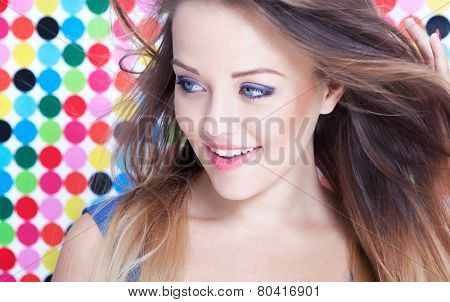 Attractive young smiling woman on spotted background, beauty and fashion concept