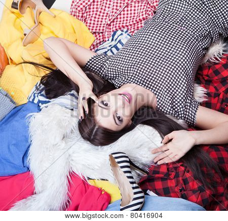 Fashion concept young attractive woman lying down on a pile of clothes and shoes