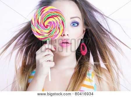 Young attractive surprised woman with a candy lollypop