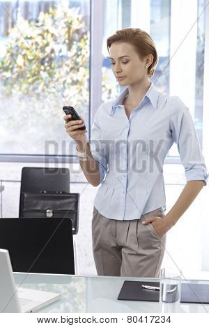 Young businesswoman writing text message on mobilephone, standing at desk with hand in pocket.