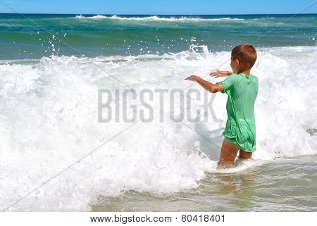 Happy Boy Playing In The Waves