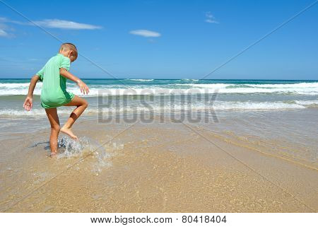 Young Boy Playing On The Beach
